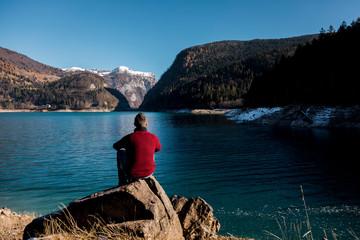 Man walking down a cliff along a lake on mountains