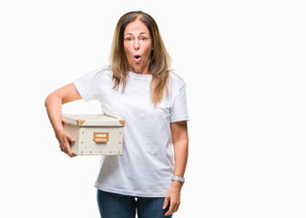 Middle age hispanic woman moving holding packing box over isolated background scared in shock with a surprise face, afraid and excited with fear expression