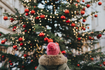 Girl with green parka and pink beanie standing in front of a christmas tree