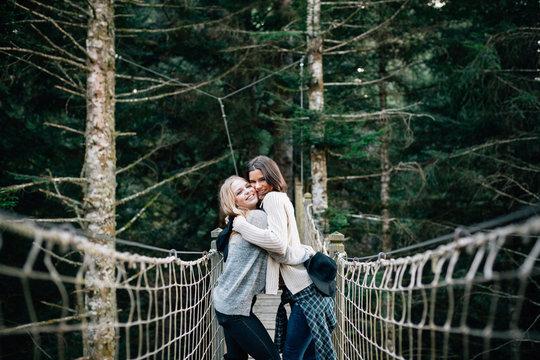 Two woman enjoying her friendship at bridge between trees.