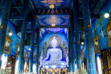 White Buddha statue in blue temple with beautiful Thai handicraft pattern.