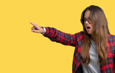 Young beautiful brunette woman wearing jacket and glasses over isolated background Pointing with finger surprised ahead, open mouth amazed expression, something in front