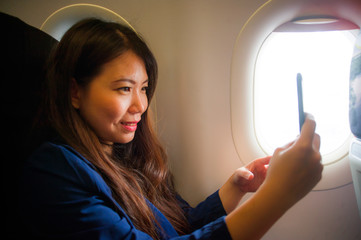 young happy and beautiful Asian Chinese woman traveling for business inside airplane cabin smiling cheerful using mobile phone taking selfie self portrait picture