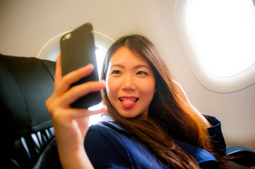 young happy and beautiful Asian Korean woman traveling for business inside airplane cabin smiling cheerful using mobile phone taking selfie self portrait picture