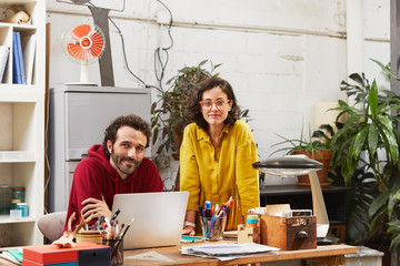 Male And Female Artists Leaning On Table In Studio