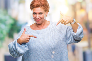 Atrractive senior caucasian redhead woman wearing winter sweater over isolated background looking confident with smile on face, pointing oneself with fingers proud and happy.