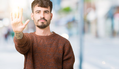 Young handsome man wearing winter sweater over isolated background doing stop sing with palm of the hand. Warning expression with negative and serious gesture on the face.