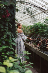 A woman in her twenties in a botanical greenhouse