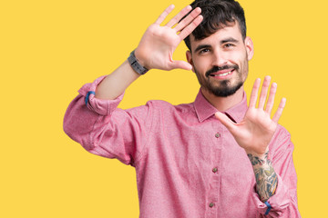 Young handsome man wearing pink shirt over isolated background Smiling doing frame using hands palms and fingers, camera perspective