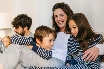 Happy mom and kids wearing pajama resting on bed.