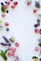 Food background with frozen berries and flowers in ice