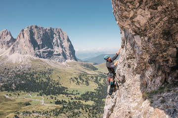 Side view of male adult rock climbing in the Dolomites.
