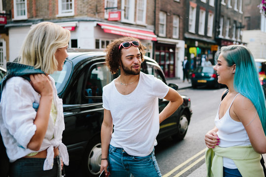 Three friends chatting in the street in a busy city