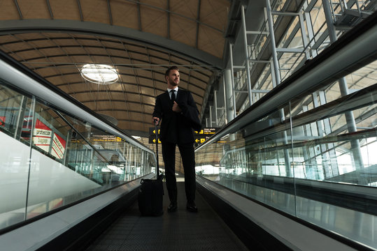 Stylish entrepreneur on moving stairs in airport