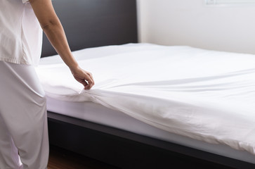 Woman make a bed,Female making white bed in room after wake up at home