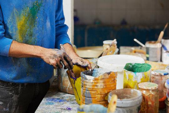 Midsection Of Artist Preparing Paint In Studio