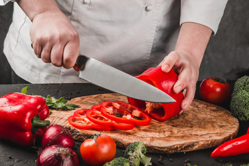 Chef cutting vegetables with knife on kitchen, cooking food. Ingredients on table. Healthy food concept. Top view