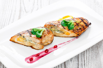 Grilled stuffed chicken breast with cheese and eggs on plate on wooden background close up. Hot Meat Dishes. Top view