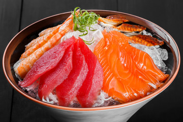 Sashimi japanese food, pieces of tuna, salmon, langoustine, smoked eel with ice in bowl on black wooden background. Fish slices. Top view