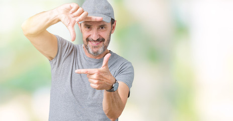 Handsome middle age hoary senior man wearing sport cap over isolated background smiling making frame with hands and fingers with happy face. Creativity and photography concept.