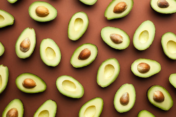 Fresh halved avocados on brown background.