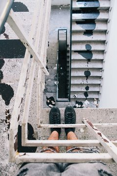 Looking down white stairwell with feet and black spilt paint