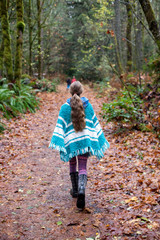 Girl in knitted poncho walks down a leaf strewn path.