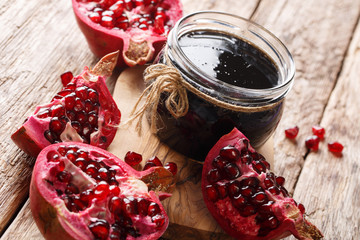 Narsharab sauce is a condensed pomegranate juice with spices in a glass jar close-up. horizontal