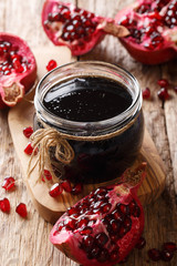 Homemade pomegranate sauce narsharab in a glass jar close-up. vertical