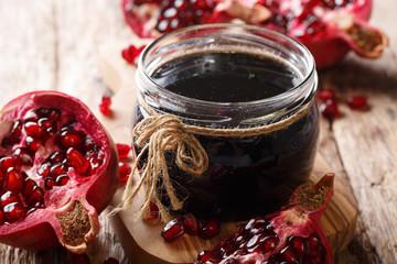 Azerbaijani seasoning Narsharab sauce made from pomegranate juice in a jar close-up. horizontal