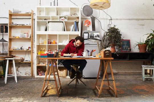 Full Length Of Artist Painting At Desk In Studio