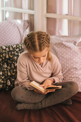 Little Girl Sitting On Bed And Reading A Book