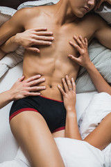 Male and female hands touching another hot man's body laying in bed