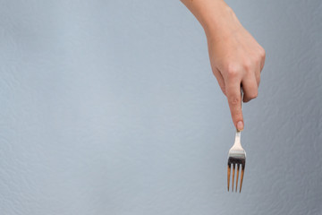 woman hand holding fork on gray background. Eating gesture.