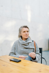 Elegant senior woman at table in cafe
