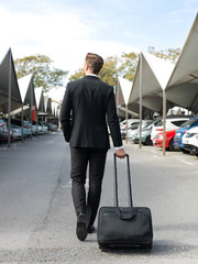Man on airport parking with suitcase