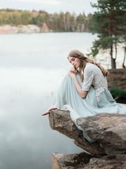 Pure beautiful model in dress on rock