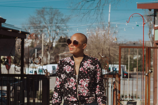 Bald African American woman wearing a flower patterned bomber jacket and big round sunglasses.