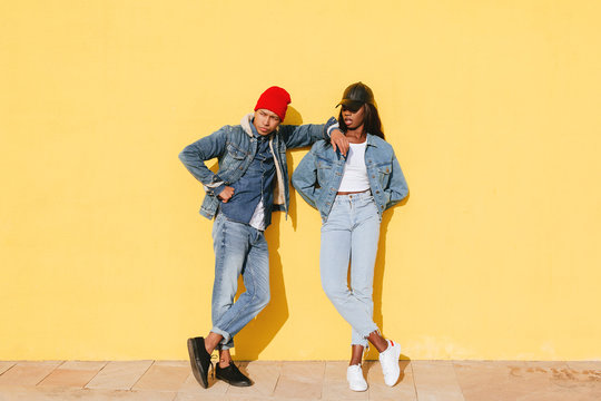 Portrait of cool couple wearing denim clothes in yellow wall.