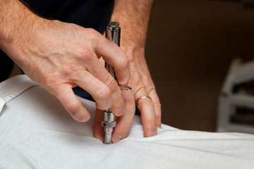 Hands of a Chiropractor Using an Integrator to Adjust the Spine of a Patient