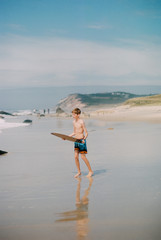teen boy with skim board at the beach
