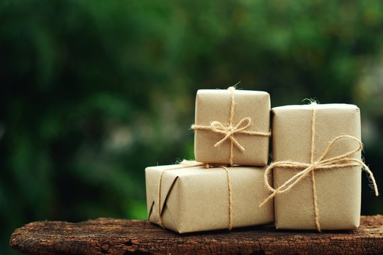 Simple eco friendly gift boxes package wrap with brown paper, green present concept, copy space