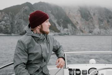 yang men wearing red hat and gray raincoat sits on the boat in the open sea