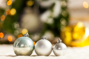 Three Pearl Christmas balls with colorful bokeh