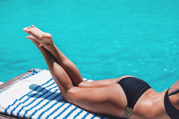 Young slim woman's legs in bikini relax near swimming pool in sun lounger