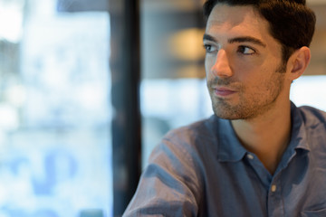 Man sitting and looking through window while thinking