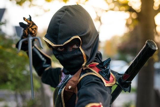 Boy dressed as a ninja makes a threatening face
