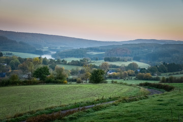 Mist in the Ardennes hills with autumn forest and village Belgium