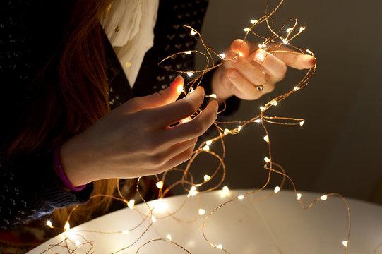 Girl untangles light garland