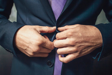 Buttoning a jacket hands close up. Stylish man in suit fastens buttons and straightens his jacket preparing to go out. Preparing for a wedding